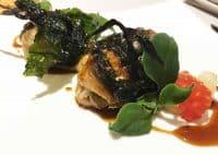 Anguilla croccante cotta allo spiedo con alghe marine croccanti su salsa di ali di pollo e semi di pomodoro